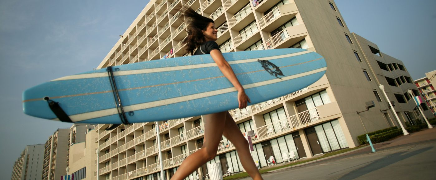 Woman with surfboard in front of hotel